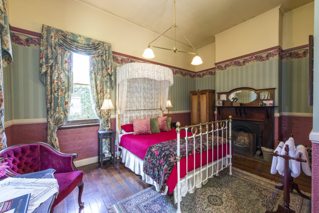 Queen ensuite room with a fireplace